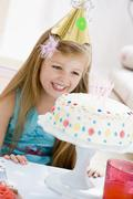 Young girl wearing party hat looking at birthday cake smiling - stock photo