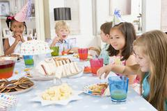 Young children at party sitting at table with food smiling - stock photo
