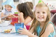 Stock Photo of Young girl at party sitting at table with food smiling