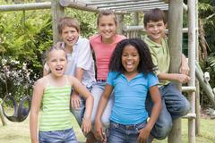 Five young friends at a playground smiling Stock Photos