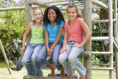 Three young girl friends at a playground smiling - stock photo