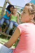 Two young girl friends at a playground whispering about other girl in foreground Stock Photos