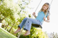Young girl sitting on swing smiling - stock photo