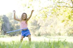 Young girl with hula hoop outdoors smiling - stock photo