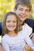 Brother and sister sitting outdoors smiling Stock Photos