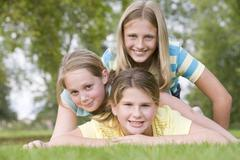 Three young girl friends piled on each other outdoors smiling - stock photo