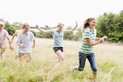 Five young friends running in a field smiling - stock photo