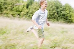 Young boy running in a field smiling Stock Photos