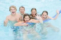 Five young friends in swimming pool playing and smiling Stock Photos