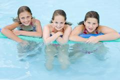 Three young girl friends in swimming pool with pool noodle smiling Stock Photos
