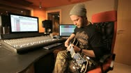Stock Video Footage of Handsome rocker playing electric guitar in recording studio - tracking shot