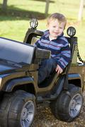 Young boy playing outdoors in toy truck smiling - stock photo