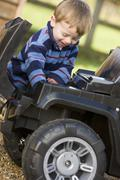 Young boy playing outdoors with toy truck smiling - stock photo