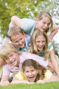 Five young friends piled on each other outdoors smiling - stock photo