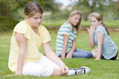 Two young girls bullying other young girl outdoors - stock photo