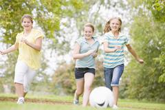 Three young girl friends playing soccer Stock Photos