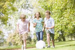 Three young friends playing soccer - stock photo