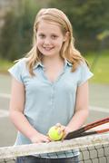 Young girl with racket on tennis court smiling Stock Photos