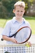 Young boy with racket on tennis court smiling Stock Photos