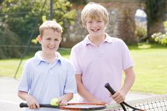 Two young male friends with rackets on tennis court smiling Stock Photos