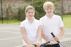 Two young friends with rackets on tennis court smiling Stock Photos
