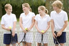 Four young friends with rackets on tennis court smiling Stock Photos