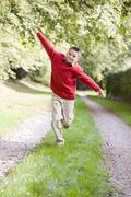 Young boy running on a path outdoors smiling Stock Photos