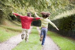Two young friends running on a path outdoors - stock photo