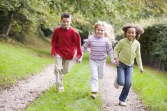 Three young friends running on a path outdoors smiling Stock Photos