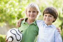 Two young boys outdoors with soccer ball smiling Stock Photos