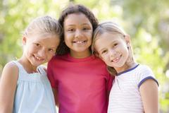 Three young girl friends standing outdoors smiling - stock photo