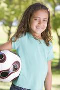 Young girl holding soccer ball outdoors smiling Stock Photos
