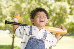 Young boy holding baseball bat outdoors smiling Stock Photos