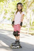 Young girl outdoors on inline skates smiling Stock Photos