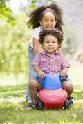 Sister pushing brother on toy with wheels smiling Stock Photos