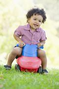 Young boy playing on toy with wheels outdoors Stock Photos