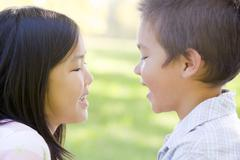 Brother and sister outdoors staring at each other and smiling Stock Photos