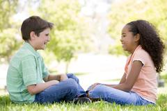 Tow young friends sitting outdoors looking at each other and smiling Stock Photos