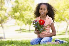 Young girl holding flowers and smiling - stock photo