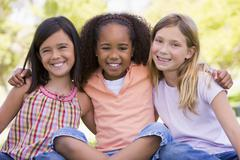 Three young girl friends sitting outdoors smiling Stock Photos
