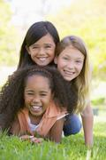 Three young girl friends piled up on top of each other outdoors smiling - stock photo