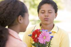 Young boy giving young girl flowers and puckering up - stock photo