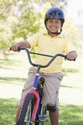 Young boy on bicycle outdoors smiling - stock photo