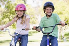 Brother and sister outdoors on bicycles smiling Stock Photos