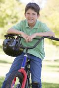Young boy on bicycle outdoors smiling Stock Photos