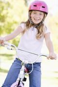 Young girl on bicycle outdoors smiling - stock photo