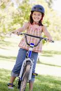 Young girl on bicycle outdoors smiling Stock Photos