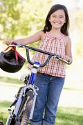 Young girl with bicycle outdoors smiling - stock photo