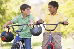 Two young boys on bicycles outdoors smiling Stock Photos