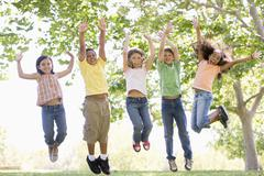 Five young friends jumping outdoors smiling - stock photo